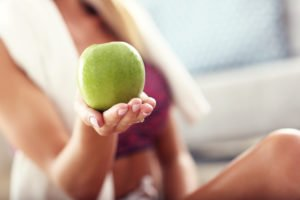 woman after pilates holding apple snack