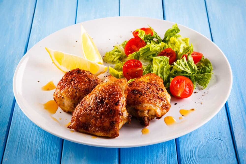 large serving of pan fried chicken thighs with salad and lemon wedges
