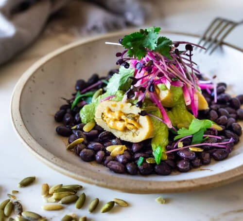 butternut squash tamales with pepita and cilantro sauce on black beans